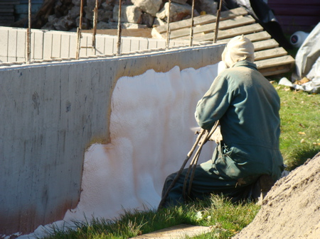 Rick spraying the foam on the foundation wall.