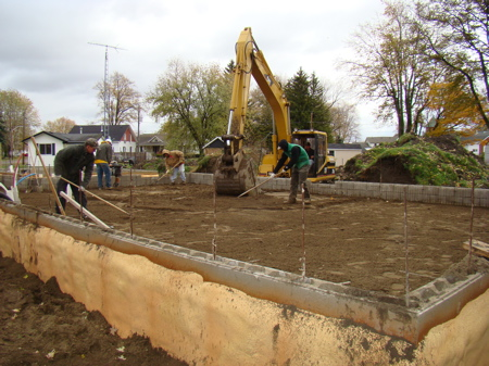Filling, leveling and packing sand in house foundation.