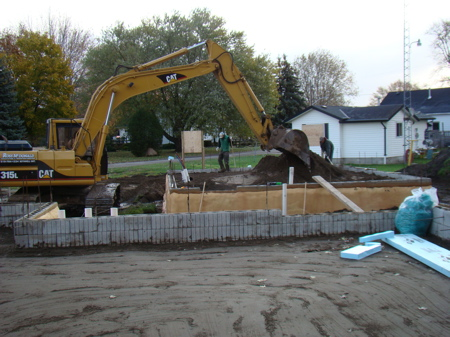 Continuing filling and packing the final layer of sand in the garage foundation.