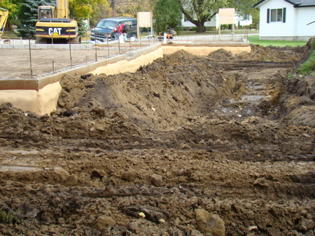 Backfilling along the south wall of the house foundation.