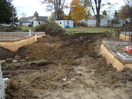 Backfilling between the house and garage foundations.