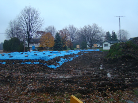 Looking along the south side, with both tarps in place over the foundation.