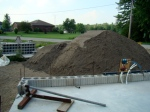 Two dump truck loads of sand fill on the edge of the driveway.