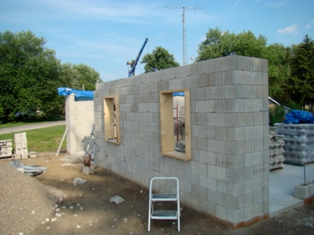 Friday July 24, North wall, at full height, half of re-inforcing cores and window lintels filled with concrete.