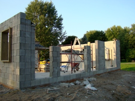 August 2, Sunday; the column and lintel pour is complete on West wall, south wall columns nearly done to top of windows. Narrow columns poured at 6 courses high for stability, the rest will be poured when the lintels are poured.