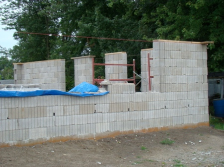 Saturday, August 22, west wall and NW corner to first window, blocks to the top of window ready for framing.
