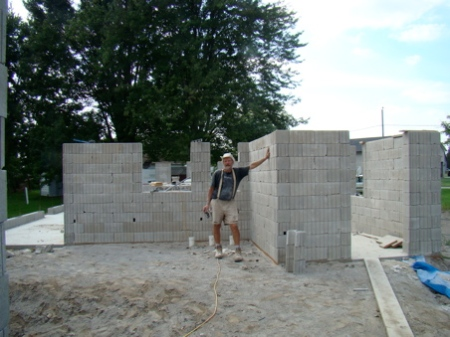 Tuesday afternoon Aug 25, finished stacking east, west, and north walls to top of window frames. Beginning to really look like a house.