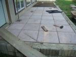 Patio blocks about half in place.  Note the landscaping fabric on sand surface to keep weeds from growing in cracks.  Also my high-tec gandy dancers compactor to the left.