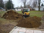Digging away at the smaller pile of topsoil.
